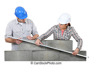 Two masons working on a wall.