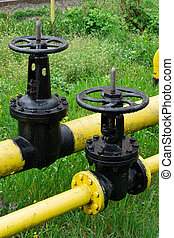 two massive black valves on a yellow gas pipe