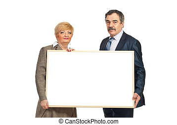 Two mature business people hold blank banner