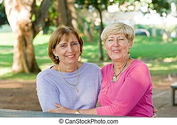 mature woman - two mature woman posing in garden