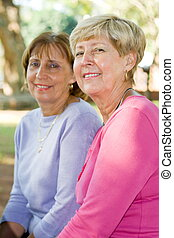 mature woman - two mature woman smiling in park