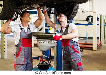 Two mechanic changing oil in a car workshop