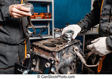 Two mechanic holding a new piston for the engine, overhaul.....