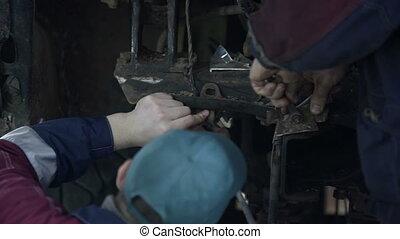 Two mechanic men repairing bus at workshop