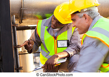 two mechanical engineers working on fuel pipeline in plant