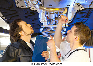 Two mechanics at work. Two confident auto mechanic working at the repair shop and discussing something while one of them holding a clipboard