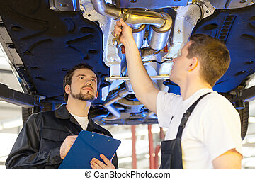 Two mechanics at work. Two confident auto mechanic working at the repair shop while one of them holding a clipboard
