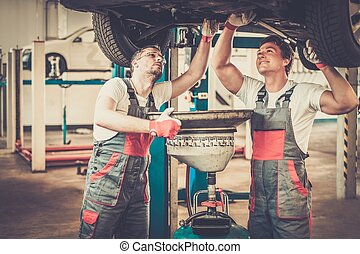 Two mechanics changing oil in a car workshop