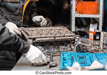 Two mechanics disassembling the engine, overhaul.. Engine on...