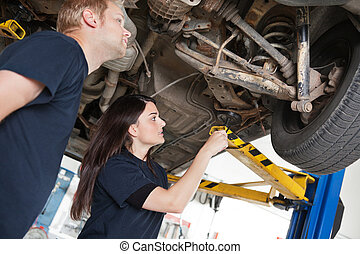 Two Mechanics Discussing Problem - Two mechanics looking at...