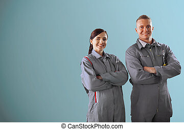 Two mechanics standing on a blue background