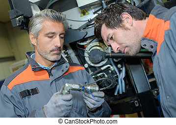 two mechanics working at workshop
