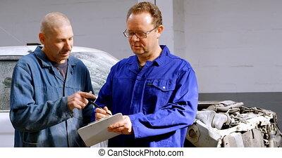 Two mechanics writing on clipboard 4k - Two mechanics ...