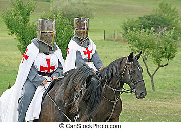 two medieval crusaders shall strutting with their horses blacks