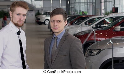 Two men against background of car salon with new models of transport. slow motion.