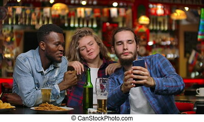 Two men and a woman look at the phone screen while sitting in a bar and prepare to take a shared selfie. Cheerful youth company at the bar