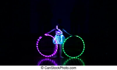Two men and a woman performes light show.