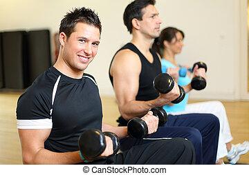 Two men and one woman exercising with dumbbells on...