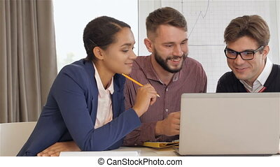Two men and one woman look at the laptop