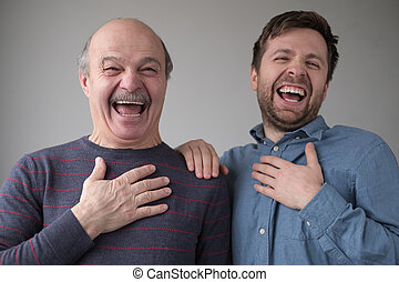 Two men and son laughing on their friend joke having a good mood.