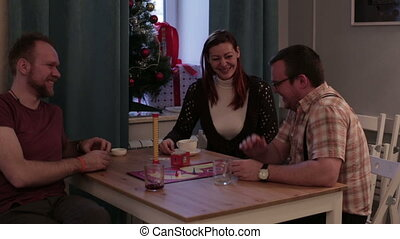 Two men and woman play a board game in a cafe