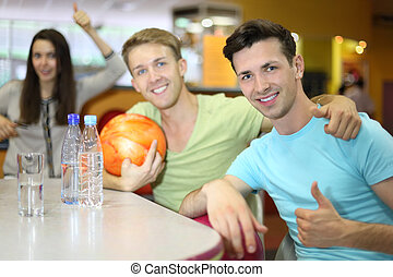 Two men and woman with balls sit at table in bowling and...