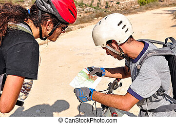 Two cyclist men read the map on the bycicle trail