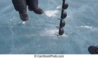 Two men are drilled ice ice screws. - Two men trying to...