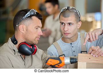 two men are drilling wood