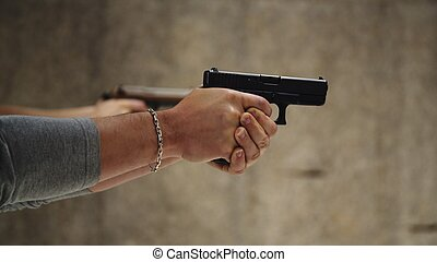 Two men are practicing shooting with hand pistol at the shooting range