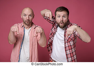 Two men are shocked by what they saw, they are in amazement pointing the index finger down and look at the camera with big eyes.