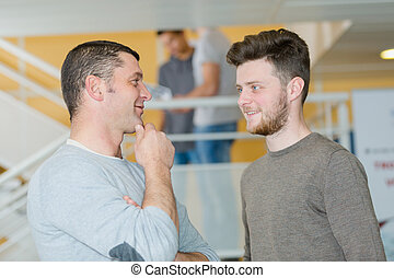 two men are talking in the corridor