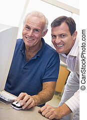 Two men at computer smiling (high key)