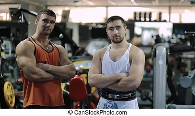 two men athlete, professional powerlifter and bodybuilder with years of experience in the hall stand and look at the camera hard to breathe,