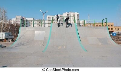 Two men BMX riders going downhill in the skatepark . Mid...