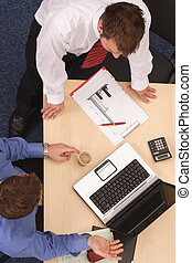 An overhead shot of two male executives in a business meeting.