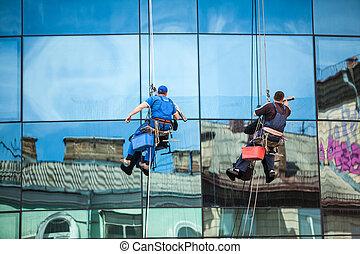 men cleaning window facade of skyscraper
