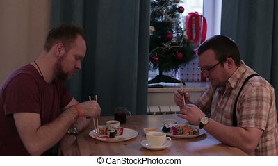 Two men eating sushi at the table