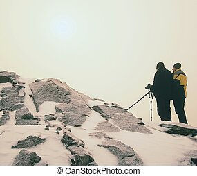 Two men enjoy winter photographying in snowy mountains. Nature photographer