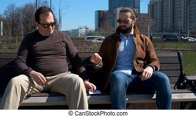 Two men exchange envelope outdoors - Two men exchange...