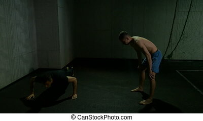 Two men fighters warming up and training in gym doing push ups and kick boxing exercises