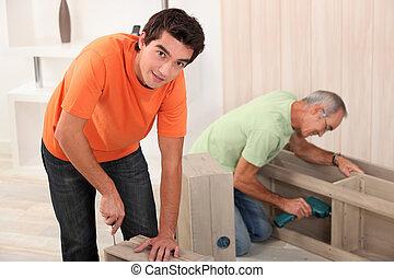 two men fixing furniture