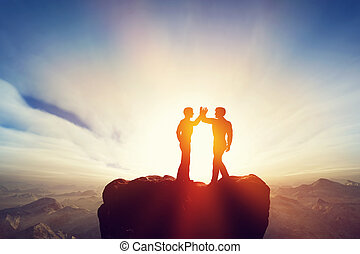 Two men, friends high five on top of the mountains....