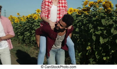 Two men girlfriends piggyback rides cheerful couple young friends summer sunny day young people group countryside road