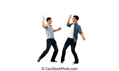Two men giving each other a high-five in slow motion