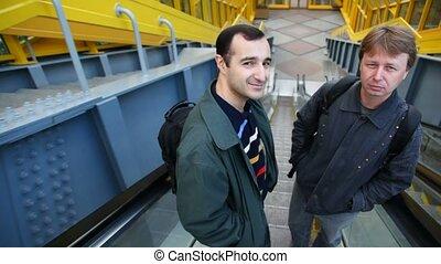 Two men go down escalator facing backwards in subway and hug