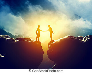 Two men handshake over mountains precipice. Business deal