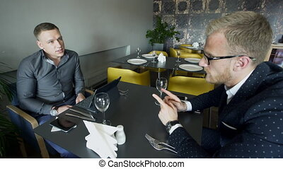 Two men have lunch speak in break up sitting at cafe indoors