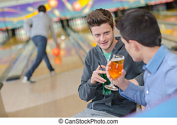 Two men having a drink at the bowling alley