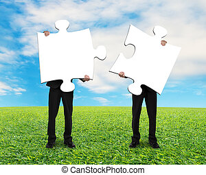 Two men holding blank puzzles on grass ground with blue sky
